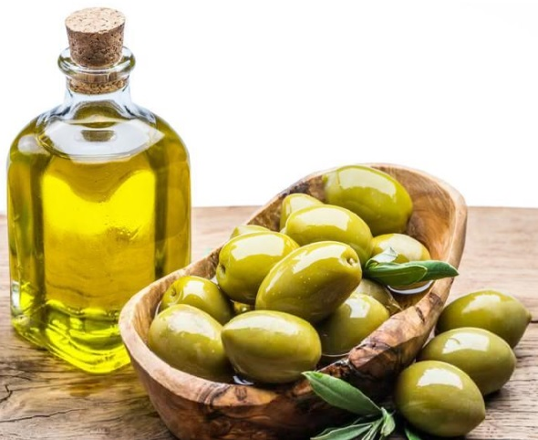 olive oil health benefits: olive oil in a bottle with fresh olives in a basket.