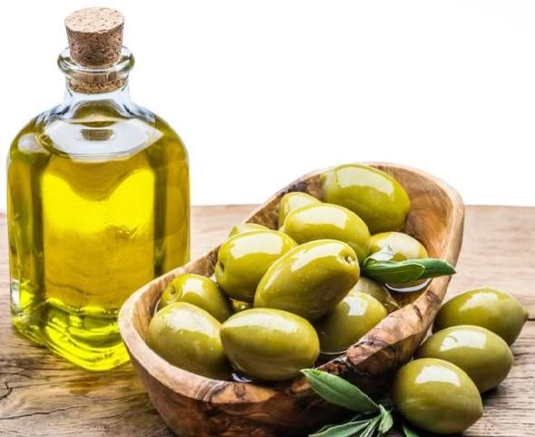 olive oil health benefits: olive oil in a bottle with fresh olives in a basket.