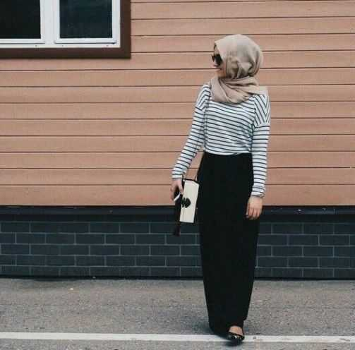 Girl wearing  nude color hijab and strip shirt and black skirt holding bag in her hand