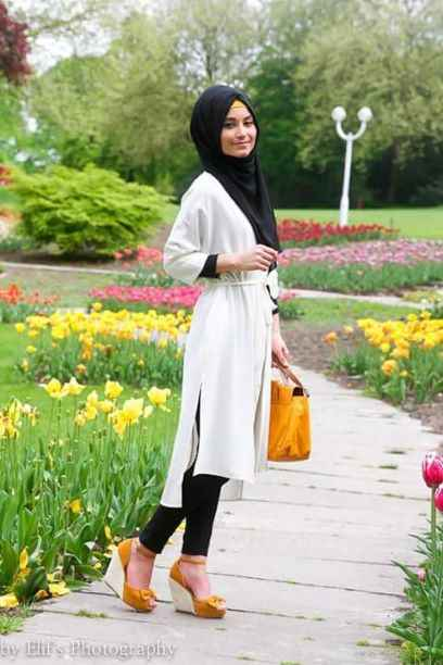 girl with hand bag and  black hijab standing in a garden